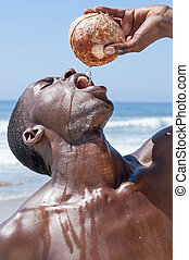 Real fresh coconut water - Closeup of shirtless muscular...