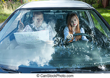 Man with map navigating woman in car