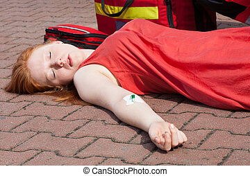 Unconscious girl with intravenous cannula in her arm