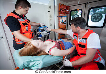 Paramedics applying first aid in ambulance - Paramedics...