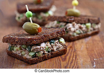Tuna salad sandwich with pumpernickel bread and cucumber