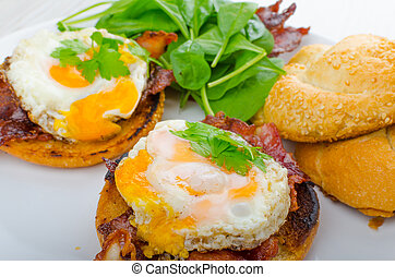 Eggs benedict with bacon and spinach on white plate