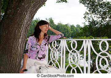 Mature woman dreaming on a bench - Attractive mature woman...