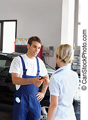 mechanic - Rear view of woman giving credit card to...