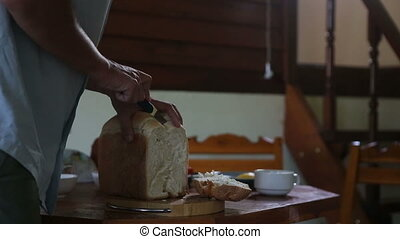 man cuts off white bread crust and smelling it