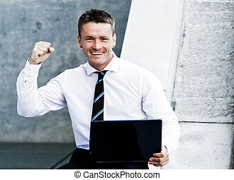 Young Elated Corporate Man With Laptop