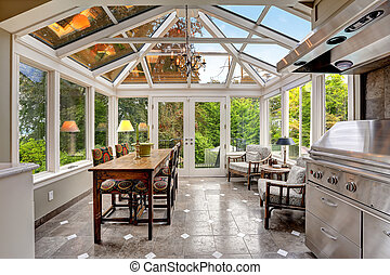 Sunroom patio area with transparent vaulted ceiling, steel...