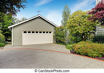Garage with concrete driveway with trees alongside