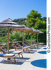 Wooden deck chairs and umbrellas near infinity pool in luxury resort