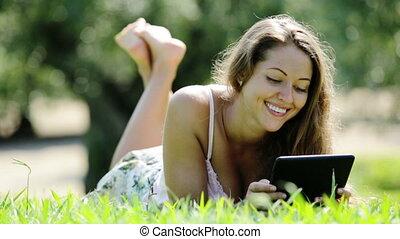 girl reading ereader - girl reading ereader at sunny park...