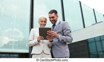 smiling businessmen with tablet pc outdoors