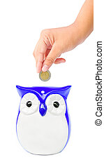 hand putting coin into a owl bank isolated on white...