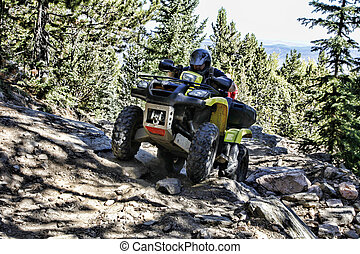 ATV Rider on Mountain Trail - ATV rider concentrates...