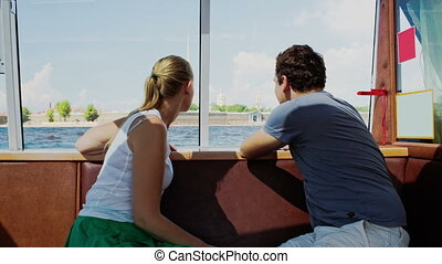 Young couple traveling by touristic boat - Young man and...