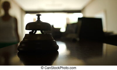 Woman ringing reception bell in hotel - Close-up shot of...