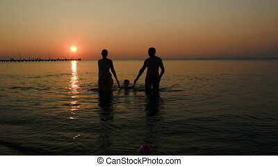 Family silhouettes coming out of sea at sunset three people