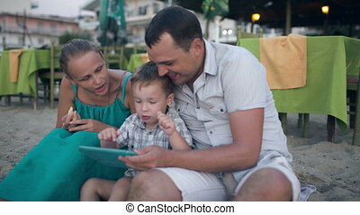 Family of three on resort with tablet PC