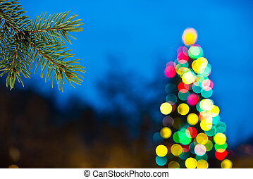 Christmas Background - a color unfocused christmas tree at...