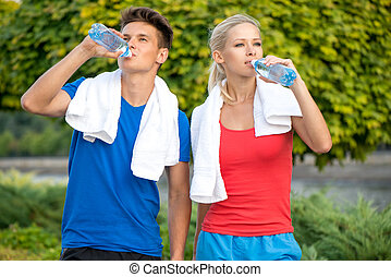 Couple drinking water after running
