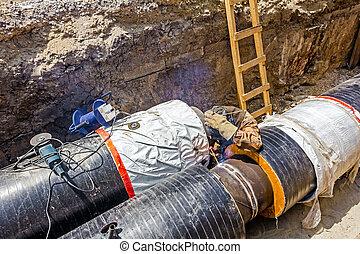 Welder is welding the pipeline in trench - Metal worker...