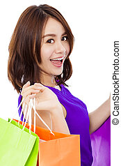 closeup of smiling young woman holding shopping bag
