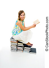 Woman reading book sitting on pile of them - Young woman...