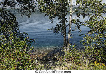 Tranquil Blue Lake - Tiny ripples glide across surface of...