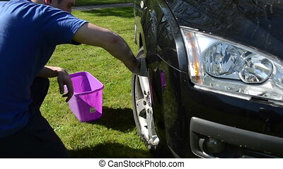 car wheel wash - man carefully wash his favourite car wheels...