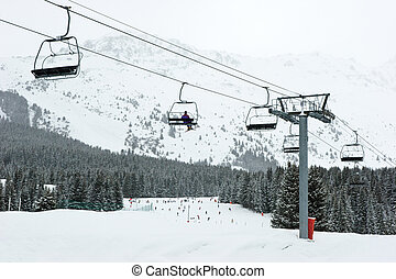 Skilift - Chairlift with skier at Meribel ski resort, France