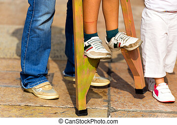 Child on Wooden Stilts - An adult helps a child to walk on...