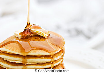 Syrup pouring onto pancakes - Maple syrup pouring onto...