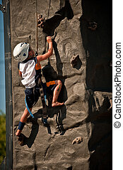 Young climber - A boy climbing up a rock wall