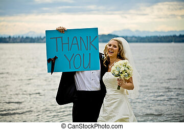 Thank you - A newly wed couple holding up a thank you sign