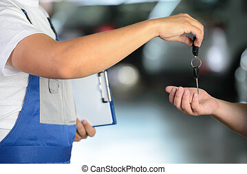 Car Service - Mechanic giving car key while shaking hand to...