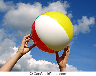 hands with beach ball against blue sky...