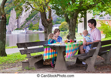 Father and kids at picnic - Happy young family, father with...