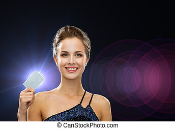 smiling woman in evening dress holding credit card -...