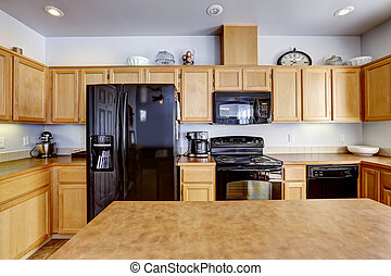 Light brown kitchen with black appliances