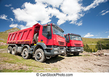 Two large red dump trucks at construction site, in a sunny...