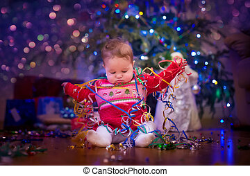 Baby under Christmas tree - Cute funny baby girl sitting...