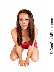 Crouching woman on floor. - A lovely young Asian woman in a...