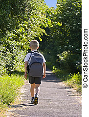 Schoolboy - Young boy wearing a backpack ready for school