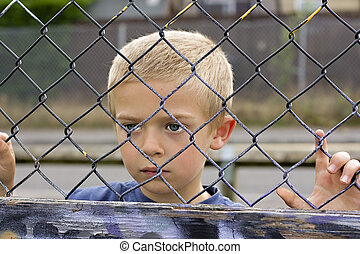 Child through fence - A portrait of a young boy looking...