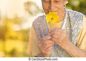 Senior woman in garden - Detail of senior woman in apron...