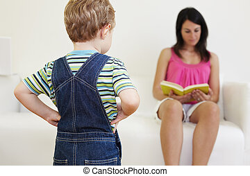 bored boy looking at mom with hands on hips