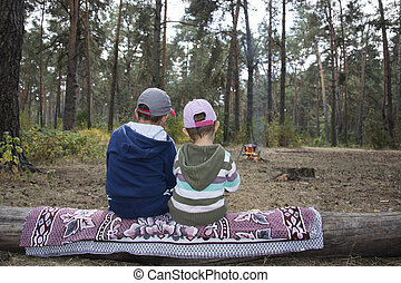 Children sitting on a log in the autumn forest and waiting...