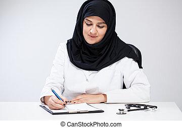 Arab female doctor noting in her office