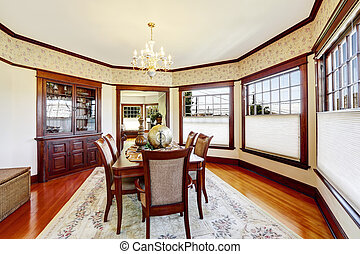 Luxury dining room with wood trim and built-in cabinet...
