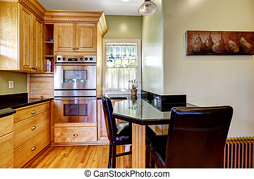 Light tones kitchen room with small dining table and chairs