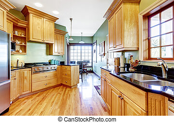 Light tones kitchen cabinets with black counter top